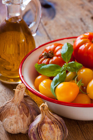 colores calidos: Tomates escogidos frescos, ajo, albahaca y aceite de oliva en colores c�lidos en una mesa de madera r�stica Foto de archivo