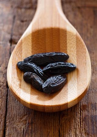 Dark aromatic tonka beans on a wooden spoon
