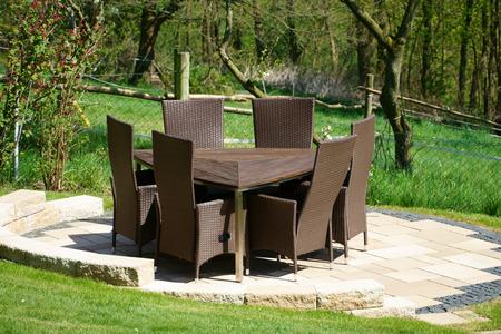 Garden furniture of rattan in the home garden Standard-Bild