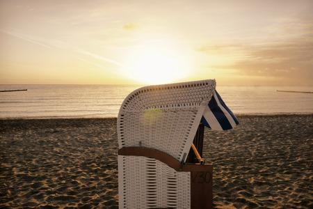 groyne: Sunrise at the Baltic Sea with a beach chair on the beach