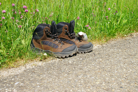 roadside stand: Hiking boots stand on the roadside beside a summer meadow Stock Photo
