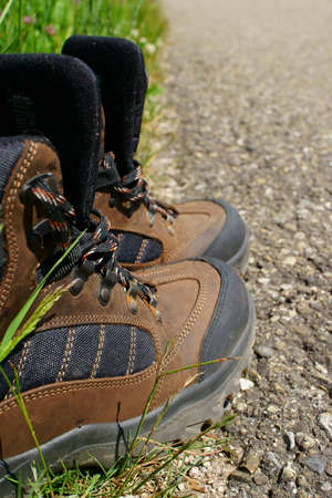 hiking boots: Close-up of Hiking boots on the roadside beside a summer meadow