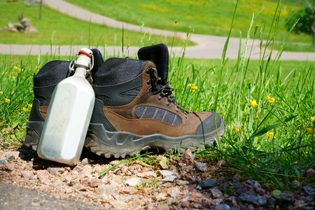 hiking boots: Hiking boots with a canteen stand on the wayside in front of a summer meadow Stock Photo