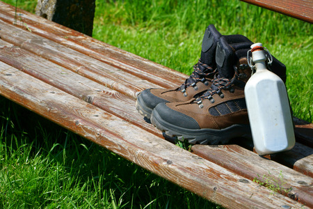 hiking boots: Hiking boots and a canteen on a seat bench in the nature Stock Photo