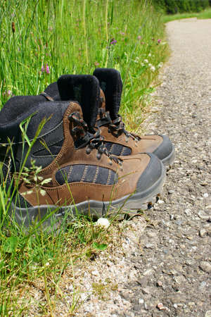 hiking boots: Hiking boots stand on the roadside beside a summer meadow Stock Photo