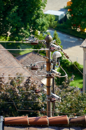 conduction: Power supply overhead line on a house roof Stock Photo