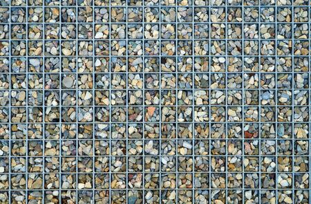 gratings: Small pebbles lie in the interstices of a metal grid Stock Photo