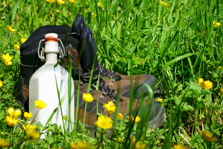 hiking boots: Hiking boots and a canteen are on a summer meadow Stock Photo