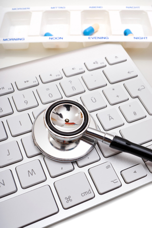 pill box: Black Stethoscope lies on computer keyboard and a pill box with labeling time of day in the background