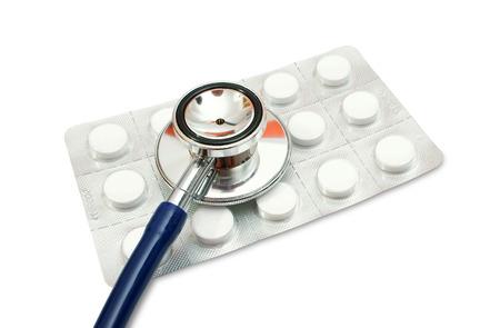 blister: Stethoscope lying on pills blister pack isolated on white background