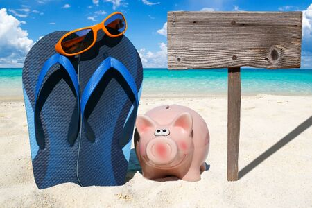 holiday budget: Pink piggy bank, Sunglasses, blue Flip Flops and a wooden Signboard on the Beach Stock Photo