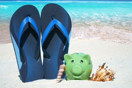 holiday budget: Green piggy bank, Seashells and blue Flip Flops on the Beach