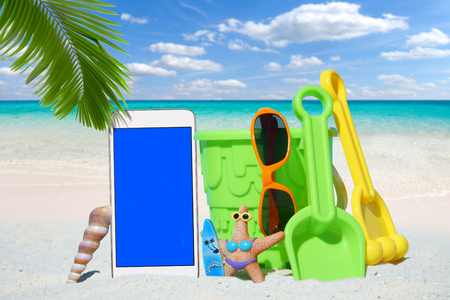 beach toys: White Smartphone with empty screen display and Beach Toys on the Sand Beach