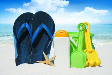 beach toys: Blue Flip Flops, Sun Cream, Beach Toys on the Beach in the summer Stock Photo
