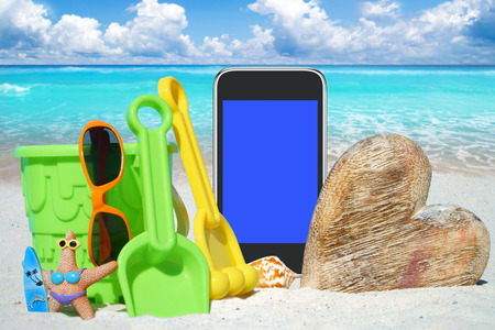 beach toys: Black Smartphone with empty screen display, wooden Heart and Beach Toys on the Sand Beach