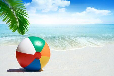 在沙滩的五颜六色的海滩球与棕榈叶