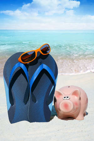 holiday budget: Pink piggy bank, Sunglasses and blue Flip Flops on the Beach