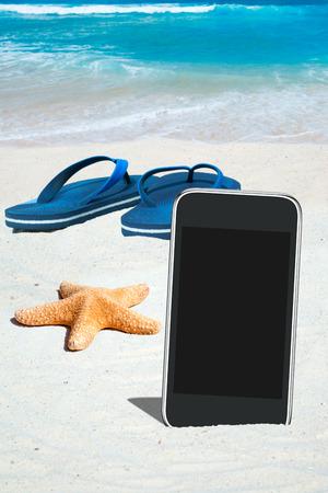 sandalias: Negro Smartphone con pantalla vacía, estrellas de mar y azul Flips Flops en la playa Foto de archivo