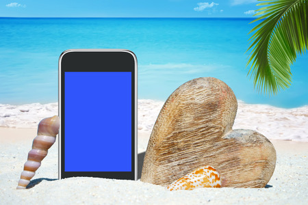 Black Smartphone with empty screen display, Seashells and a wooden heart on the Beach
