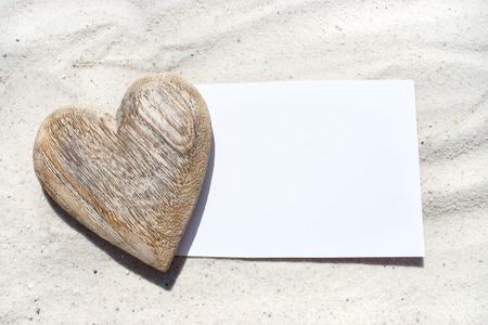White blank postcard with heart of wood on the beach Standard-Bild