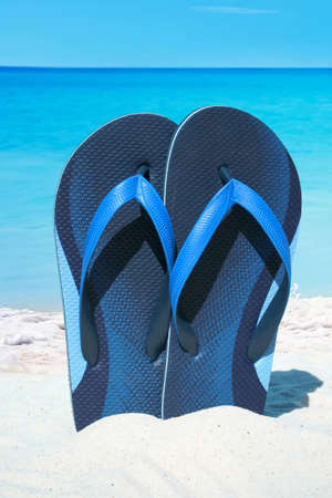 flip flops: Blue flip flops on the sunny beach with ocean in the background Stock Photo