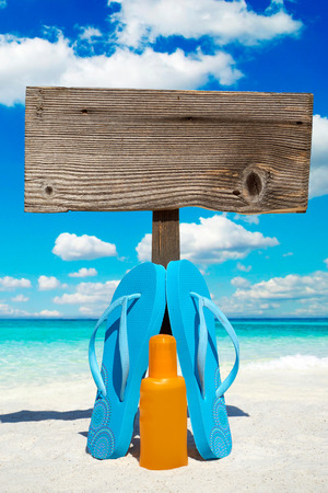 suntan lotion: Wooden signboard with copy space and flip flops with a bottle suntan lotion on the sunny beach
