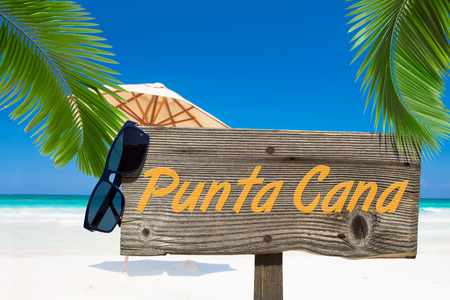 Wooden signboard with text message PUNTA CANA and a sunglasses under palm fronds on the summer beach