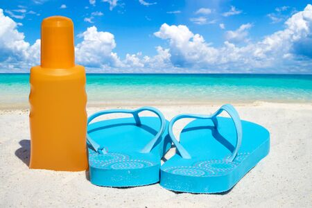flip flops: Blue Flip flops a bootle suntan lotion on the sunny beach Stock Photo