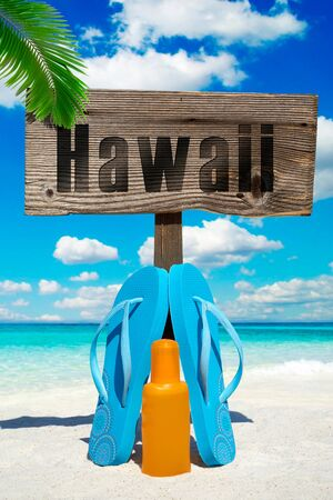 suntan lotion: Wooden signboard with the message HAWAII, blue flip flops and a bootle suntan lotion on the sunny beach