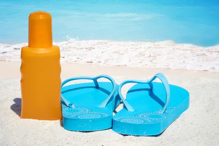bootle: Blue Flip flops a bootle suntan lotion on the sunny beach Stock Photo