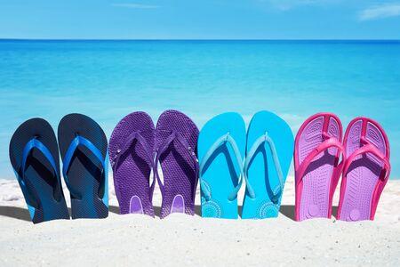 sandalias: Algunos coloridos flips flops en una fila están en la soleada playa en el verano
