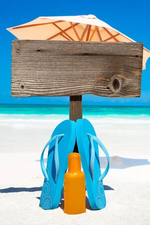 suntan lotion: Wooden signboard with copy space and flip flops with a bottle suntan lotion on the sunny beach with a sunshades in the background