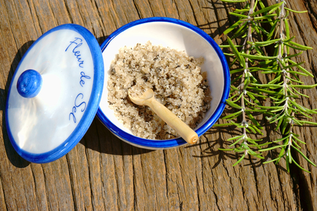 sel: Small porcelain dish with fleur de sel and a rosemary twig on a rustic wooden table
