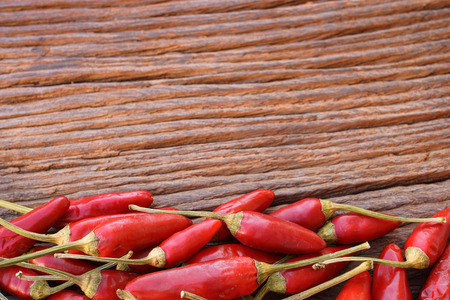 green frame: Fresh hot red chili peppers with border at the lower side as a frame on a rustic wooden background Stock Photo