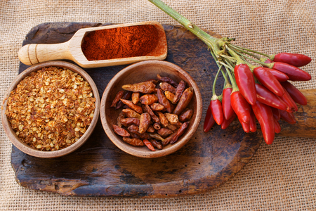 chili powder: Chili pepper, fresh pods on a bunch, dried in wooden bowl, crushed in a wooden bowl and as powder on wooden scoop is all on an old antique wooden scoop on jute fabric Stock Photo