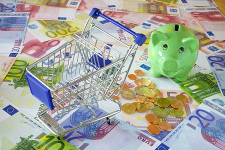 household money: Blue shopping cart and a green piggy bank on background made of euro banknotes and coins