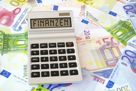 finanzen: Pocket calculator with the the german Word Finanzen (english translation � Finance) on the display. In the Background many euro banknotes Stock Photo