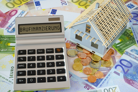 Pocket calculator with the the german Word Baufinanzierung (english translation – Mortgage lending) on the display. Model of a New building. In the background many euro banknotes and coins
