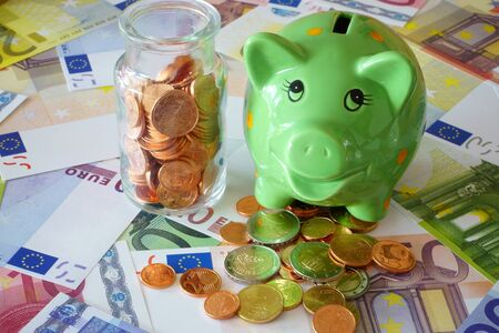 sparingly: Small glass bottle with Euro coins and a green piggy bank on background made of euro banknotes and coins Stock Photo