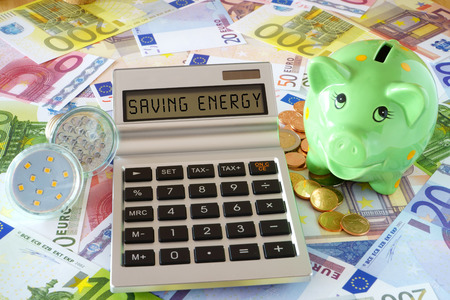 sparingly: Pocket calculator with the words Saving Power, two LED lamps and a green piggy bank on a background made of Euro banknotes and coins