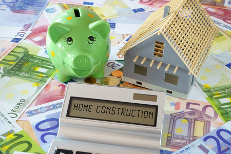 constraction: Pocket calculator with the words Home Construction on the display. Green Piggy Bank and a model of a new building on a background of Euro banknotes