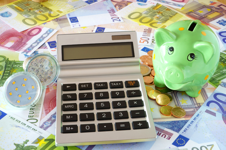 sparingly: Pocket calculator with blank display, LED lamps, green piggy bank on a background made of euro banknotes and coins