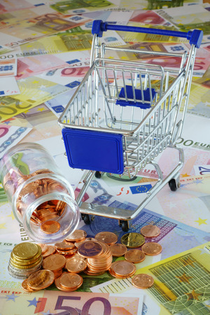 sparingly: Blue shopping cart and a small glass bottle with coins on background made of euro banknotes and coins