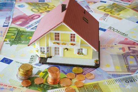 Model of a Home Ownership on a background made of Euro banknotes und coins