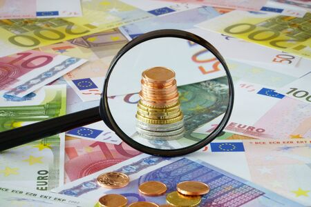 coin stack: Coin stack behind magnifying glass on a background made of Euro banknotes and coins