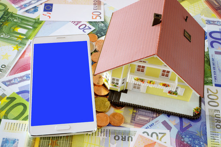 home ownership: Smart phone with blank display and a model of a Home Ownership on a background made of Euro banknotes and coins