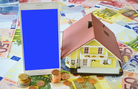 smart investing: Smart phone with blank display and a model of a Home Ownership on a background made of Euro banknotes and coins