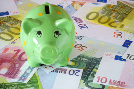 sparingly: Green Piggy Bank on a background made of Euro banknotes