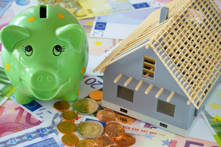 Model of a house new building and a green piggy bank on a background made of Euro banknotes and coins