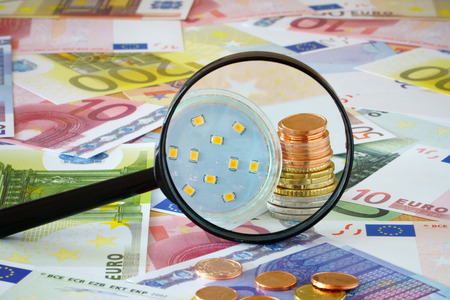coin stack: Coin stack and LED Lamp behind magnifying glass on a background made of Euro banknotes and coins